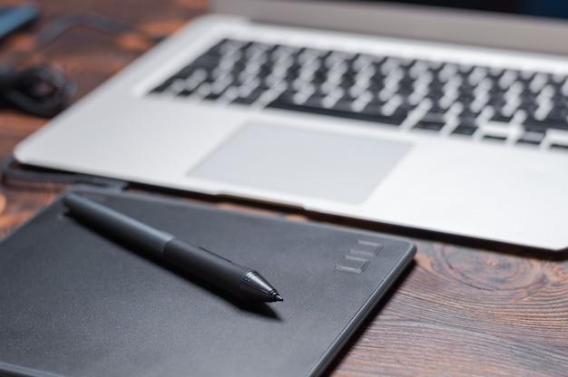 Obraz miejsca pracy retuszera. tablet graficzny, laptop, rysik. koncepcja freelance. do