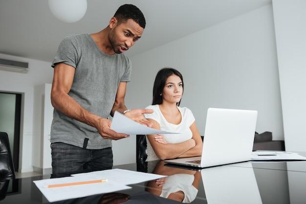 Obraz miłości para dyskutuje o rachunkach krajowych w domu. kobieta poważnie patrzeć na bok.