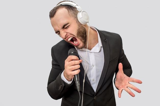 Obraz młodego człowieka krzyczącego w mikrofonie w garniturze. on śpiewa piosenkę. facet kurczy się i porusza ręką.