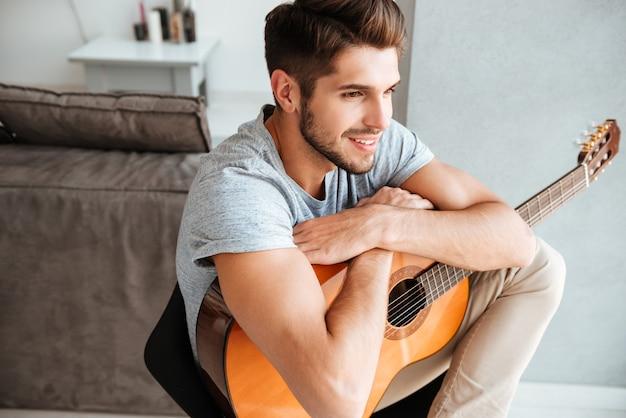 Obraz młodego człowieka siedzącego z gitarą na krześle i patrzeć na bok.