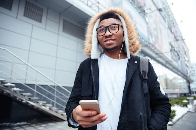 Obraz młodego człowieka trzymającego telefon w ręce i rozmawiającego podczas słuchania muzyki.