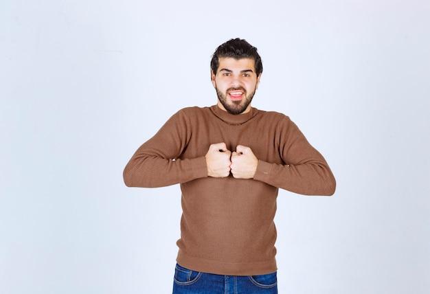 Obraz młodego mężczyzny atrakcyjnego modelu stojącego i stawiającego razem pięści. zdjęcie wysokiej jakości