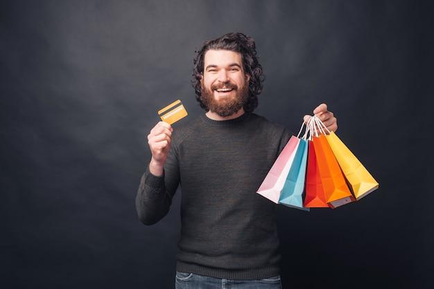 Obraz młodego mężczyzny, który poszedł na zakupy i zapłacił kartą kredytową, jest zadowolony