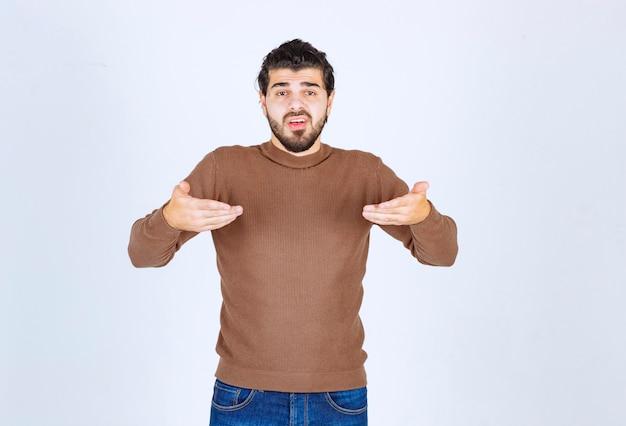 Obraz młodego mężczyzny stojącego modelu i pokazującego się na siebie. zdjęcie wysokiej jakości