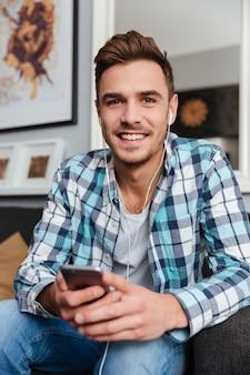 Obraz młodego mężczyzny ubranego w koszulę w nadruk klatki, siedzącego na kanapie w domu i trzymającego telefon