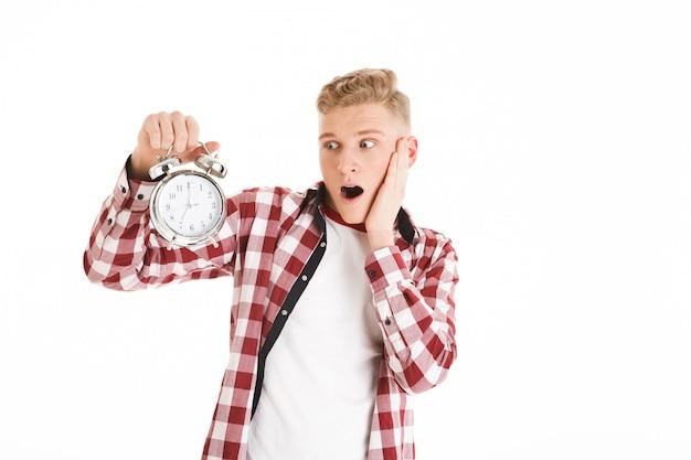 Obraz młodego modnisia mężczyzna 16y w przypadkowym mieniu i patrzeć budzika odliczającego czas dla rozkładu, odizolowywający nad biel ścianą