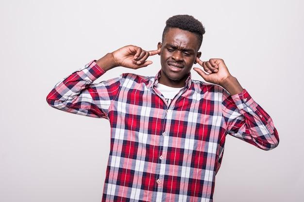 Obraz młodego niezadowolonego afrykańskiego mężczyzny stojącego na białym tle zamyka uszy od hałasu.