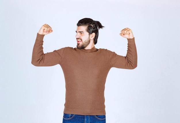 Obraz młodego przystojnego mężczyzny stojącego i pokazującego jego mięśnie. zdjęcie wysokiej jakości