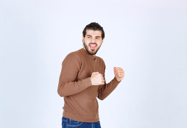 Obraz młodego, przystojnego mężczyzny stojącego modelu i pozowanie z pięściami. zdjęcie wysokiej jakości