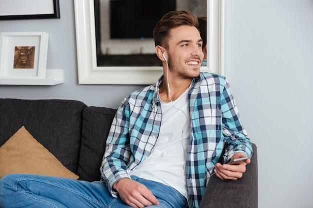 Obraz młodego śmiejącego się mężczyzny ubranego w koszulę w nadruk klatki, siedzącego na kanapie w domu i patrzącego na bok