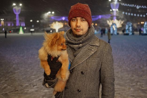 Obraz młodego uroczego mężczyzny z psem, pomorskim, na zewnątrz, pod śniegiem. zimowy czas