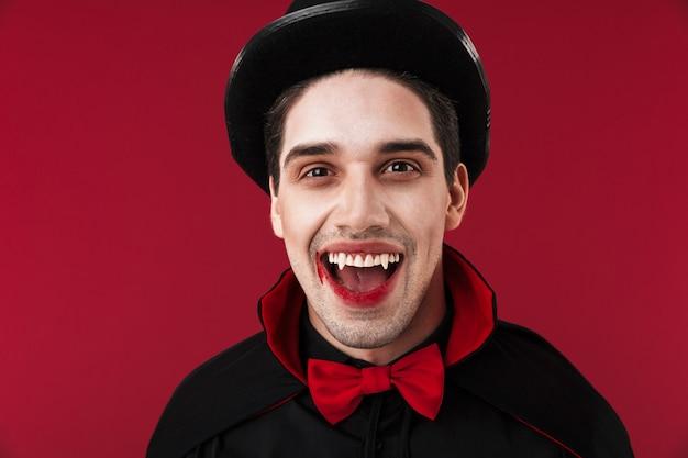 Obraz młodego wampira z krwią i kłami w czarnym kostiumie na halloween, uśmiechający się
