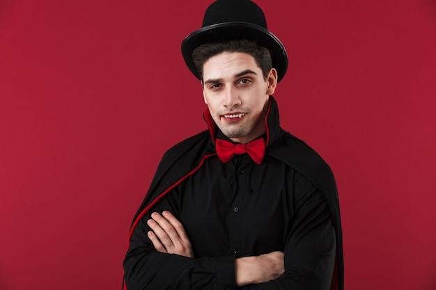 Obraz młodego wampira z krwią i kłami w czarnym kostiumie na halloween