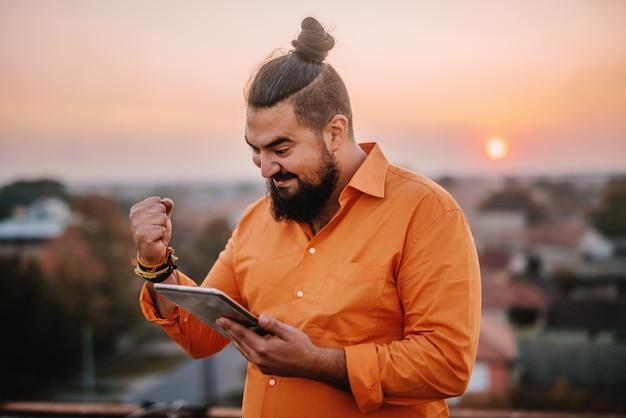Obraz młodego współczesnego człowieka stojącego na szczycie budynku
