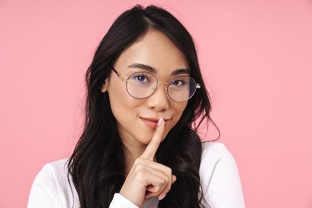 Obraz młodej brunetki azjatyckiej kobiety noszącej okulary trzymającej palec na ustach i proszącej o zachowanie ciszy odizolowanej na różowo