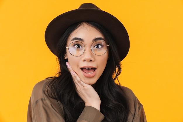 Obraz młodej brunetki azjatyckiej kobiety w kapeluszu i okularach wyrażający zaskoczenie emocjami na żółto