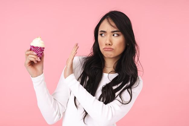 """Obraz młodej brunetki azjatyckiej kobiety z długimi włosami, gestykulującej """"nie"""", trzymającej ciastko odizolowane na różowo"""