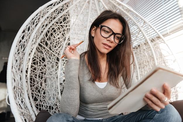 Obraz młodej damy zamyślony w okularach, siedząc na krześle w pomieszczeniu podczas pisania notatek w notesie. spójrz na notatnik.