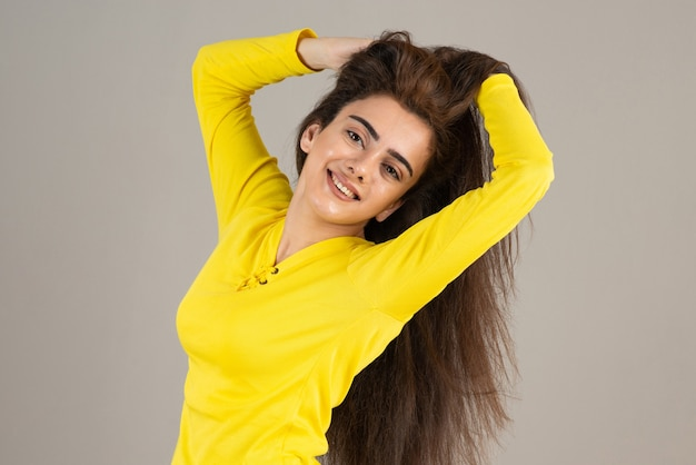 Obraz młodej dziewczyny w żółtej górze pozowanie na szarej ścianie.