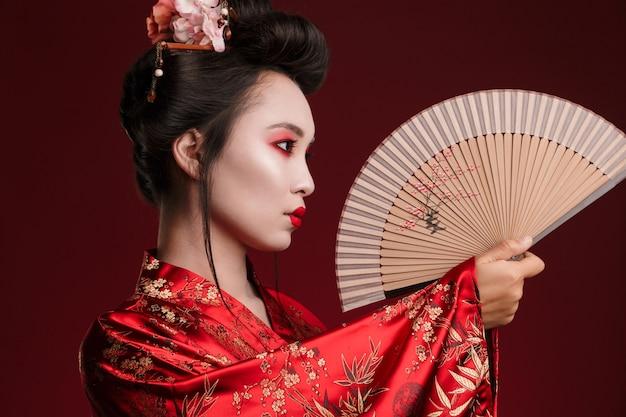Obraz młodej gejszy w tradycyjnym japońskim kimonie trzymającej drewniany wachlarz