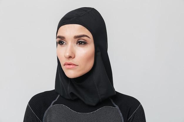 Obraz młodej kobiety fitness muzułmańskiej pozowanie na białym tle