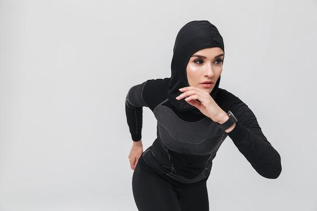 Obraz młodej kobiety fitness muzułmańskiej robi ćwiczenia na białym tle