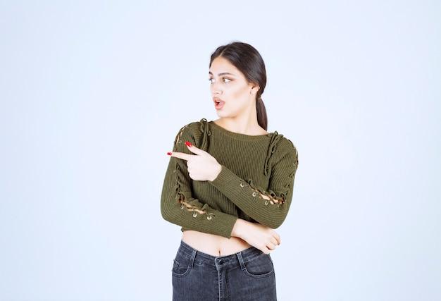 Obraz młodej kobiety model stojący i wskazujący na bok palcem wskazującym.