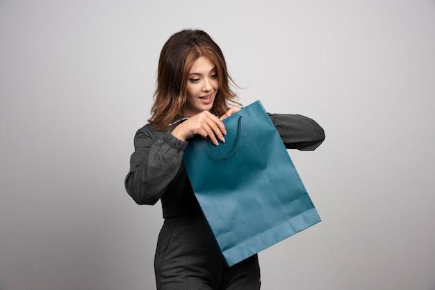 Obraz młodej kobiety patrzącej na torbę sklepową.