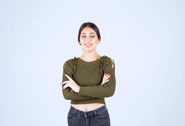 Obraz młodej kobiety stojącej, jednocześnie uśmiechając się na białym tle.