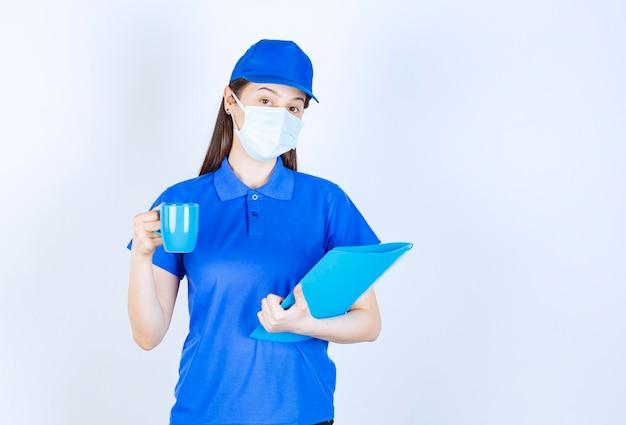 Obraz młodej kobiety w masce medycznej, trzymając niebieski folder i kubek.