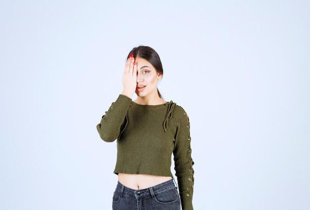Obraz młodej kobiety w szoku, zasłaniając ręką oko.