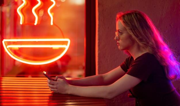 Obraz młodej optymistycznie szczęśliwej kobiety siedzącej w kawiarni na świeżym powietrzu w wieczorną noc przy użyciu telefonu komórkowego.