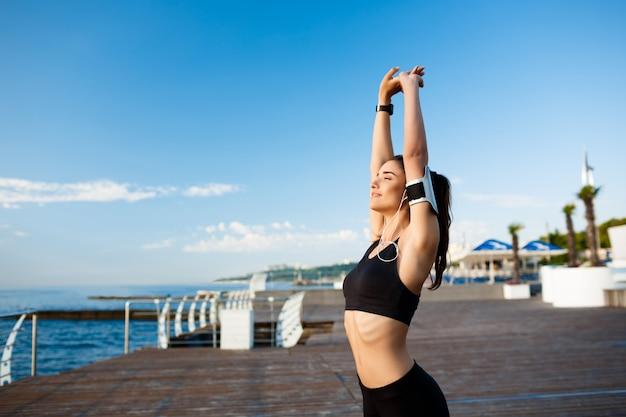 Obraz młodej pięknej fitness kobiety sprawia, że ćwiczenia sportowe