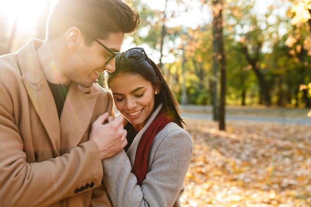 Obraz młodej szczęśliwej pary uśmiechającej się i przytulającej się podczas spaceru w jesiennym parku