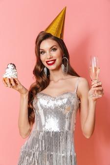 Obraz młodej uśmiechniętej optymistycznej kobiety w jasnej cekinowej sukience odizolowanej na różowej ścianie trzymającej babeczkę i kieliszek z szampanem w świątecznej urodzinowej czapce.