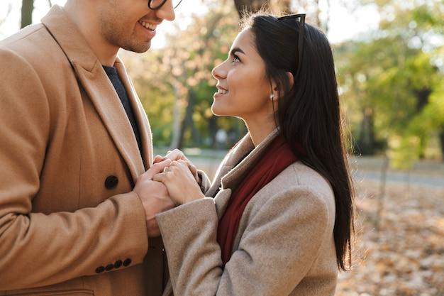Obraz młodej uśmiechniętej pary trzymającej się za ręce i patrzącej na siebie podczas spaceru w jesiennym parku