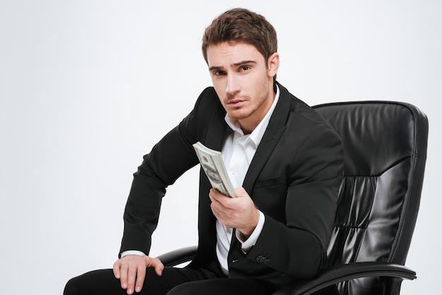 Obraz młody atrakcyjny biznesmen siedzi na krześle, trzymając pieniądze w ręce. pojedynczo na białej ścianie.