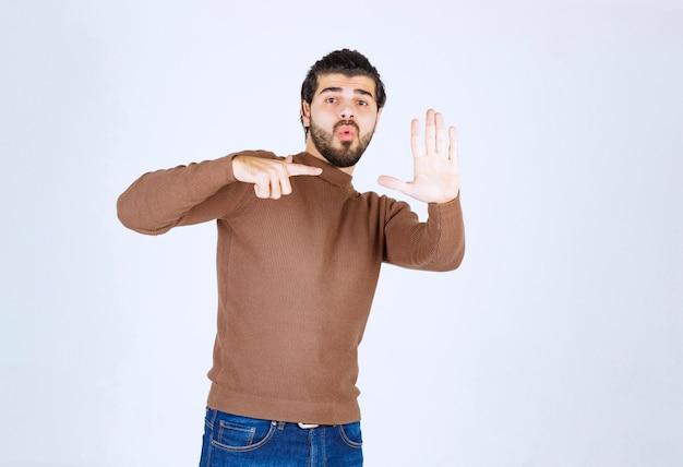 Obraz młody model mężczyzna w brązowym swetrze stojącym na białej ścianie.