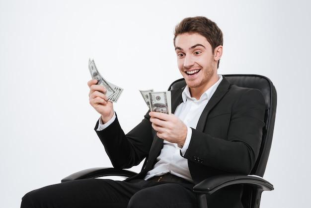 Obraz młody przystojny biznesmen siedzi na krześle, trzymając pieniądze w ręce. pojedynczo na białej ścianie. spójrz na pieniądze.