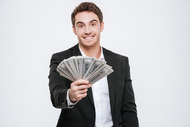 Obraz młody wesoły biznesmen stojący trzymając pieniądze w ręce. pojedynczo na białej ścianie.