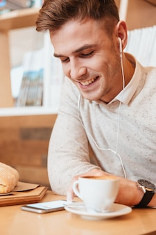Obraz młody wesoły mężczyzna ubrany w białą koszulę siedzi w kawiarni podczas słuchania muzyki ze słuchawkami i picia kawy.