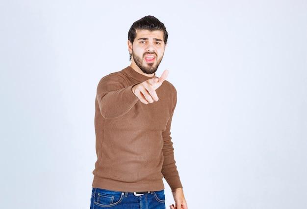 Obraz modelu młody przystojny mężczyzna stojąc i wskazując na aparat. zdjęcie wysokiej jakości
