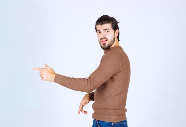 Obraz modelu młody przystojny mężczyzna stojąc i wskazując od hotelu. zdjęcie wysokiej jakości