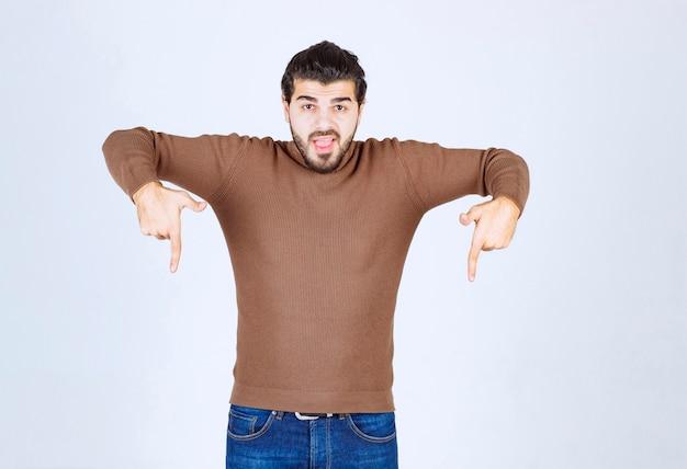 Obraz modelu młody przystojny mężczyzna stojąc i wskazując w dół. zdjęcie wysokiej jakości