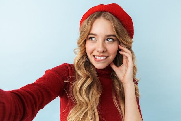 Obraz modnej blond kobieta 20s ubrana w czerwony beret, uśmiechając się podczas robienia zdjęcia selfie, na białym tle