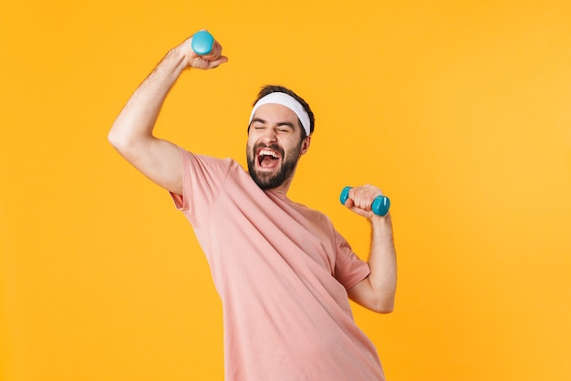 Obraz muskularnego, sportowego młodego mężczyzny w koszulce, który bawi się i podnosi hantle izolowane na żółto