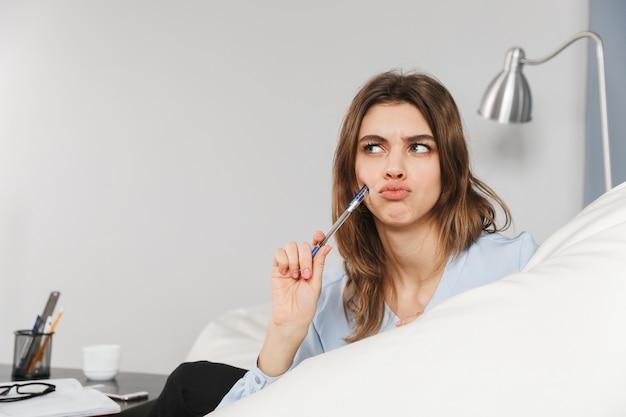 Obraz myślenia przemyślany piękna młoda ładna kobieta w domu w pomieszczeniu pisania notatek w notesie.