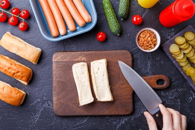 Obraz na stole ze składnikami do hot dogów, deska do krojenia, ręce mężczyzny