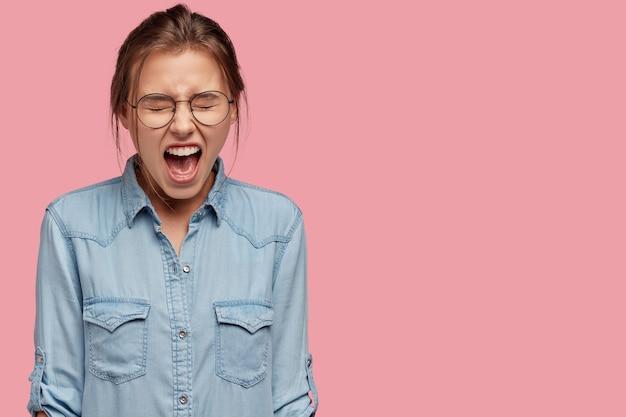 Obraz negatywnej niezadowolonej młodej kobiety wrzeszczy głośno z irytacji