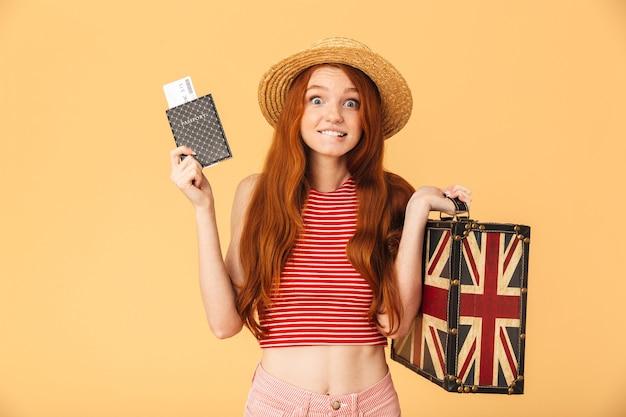Obraz nerwowej nadziei słodkiej młodej ładnej rudej kobiety pozuje na białym tle nad żółtą ścianą trzymając walizkę i paszport z biletami gryzie jej wargę.